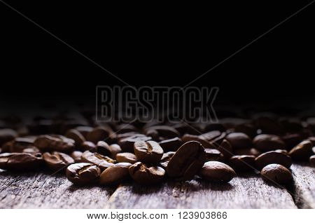 Whole coffee beans on a wooden background. Selective focus.