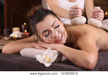 Beautiful young girl having massage with herbal balls in spa salon