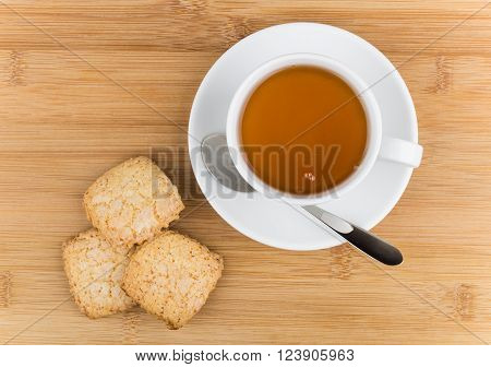 Cup of hot tea and shortbread on wooden table top view