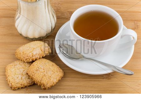 Cup of tea sugar and shortbread on wooden table