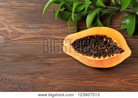 Halved papaya with leaves on wooden background