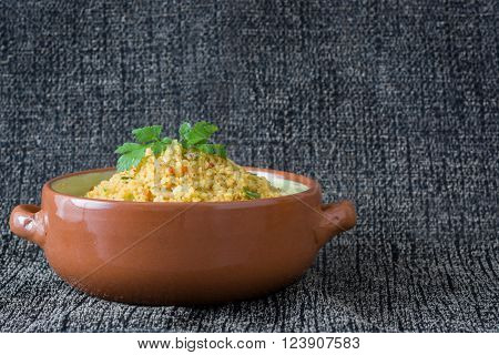 Homemade Couscous with vegetables on gray tablecloth
