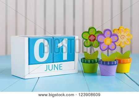 June 1st. Image of june 1 wooden color calendar on blue background with flowers. First summer day. Empty space for text. Happy Childrens Day.