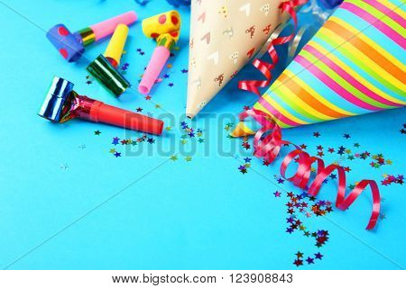Birthday hats with serpentine streamer and noise makers on blue background