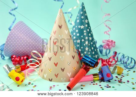 Three Birthday hats with serpentine streamer and noise makers on light blue background