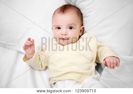 Loving baby lying on soft bed, close up