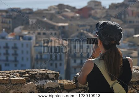 Back view on long haired woman wearing cap shooting video on amateur camera. A town in background