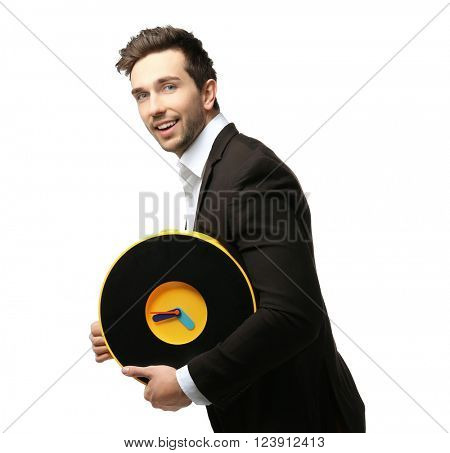 Man in black suit holding big clock is late for work on white background