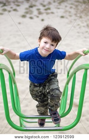Little boy climbing on jungle gym, outdoor