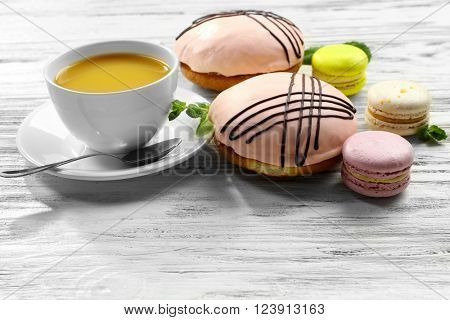 Tea with milk and macaroons on wooden background