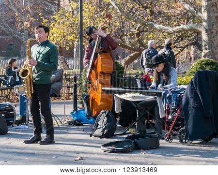 Manhattan New York - December 06 2015: Team of street musicians playing during lazy Sunday afternoon in Washington Square Park.