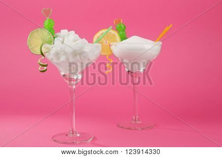 Margarita glasses with lump, granulated sugar, cocktail straws and citrus slice on pink background