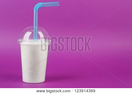 Plastic smoothie cup with granulated sugar and cocktail tube on purple background