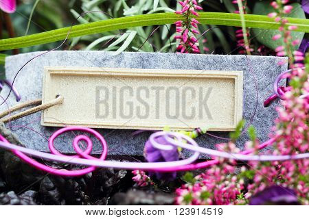 a shield lies on a stone between flowers