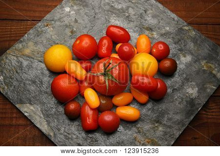 Top view of a group of Medley Tomatoes on a slab of slate on a rustic wood surface.