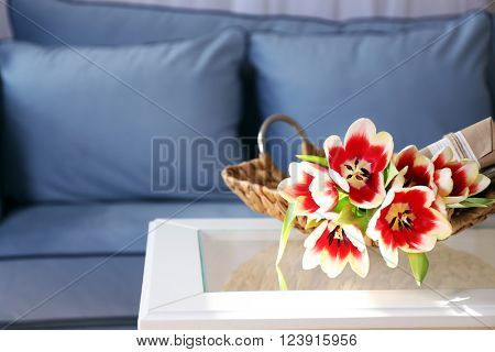 Bouquet of variegated tulips with gift box in basket on the table