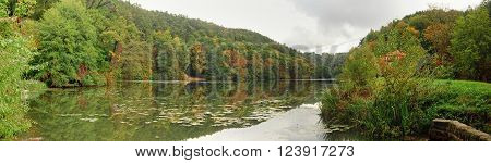 Calm surface of the lake surrounded by autumn landscape