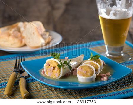 Stuffed Calamari squid served on blue ceramic plate with textural place mat with fork and knife, and a glass of beer