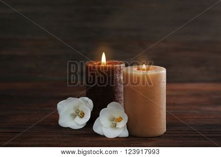 Aroma candles and beautiful flowers on wooden background