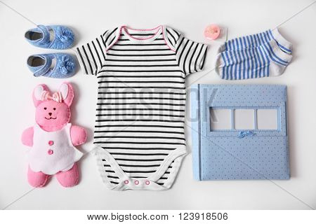 Baby clothes with toy and photo album on white background