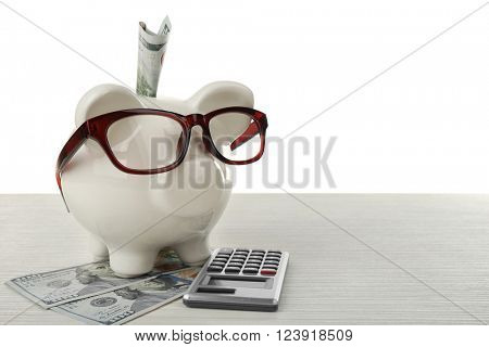 Piggy bank with inserted dollar banknote, glasses and calculator on white background