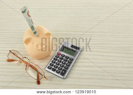 Beige piggy bank with inserted dollar banknote, glasses and calculator on light background
