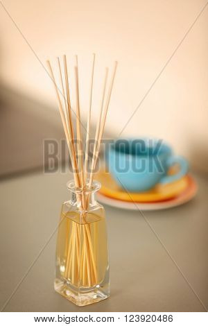 Handmade reed freshener with dishware on white table in kitchen, close up