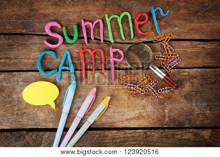 Inscription SUMMER CAMP made of colorful plasticine and stationery on wooden background
