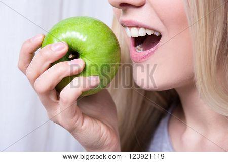 Close Up Portrait Of Woman Biting Green Apple