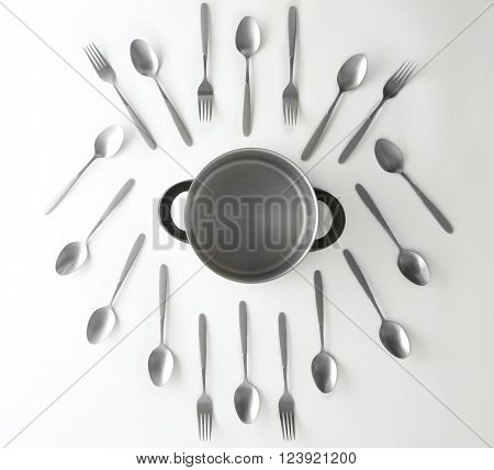 Saucepan, silver spoons and forks, top view