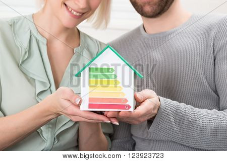 Young Couple Showing Energy Efficiency Rate On House Model
