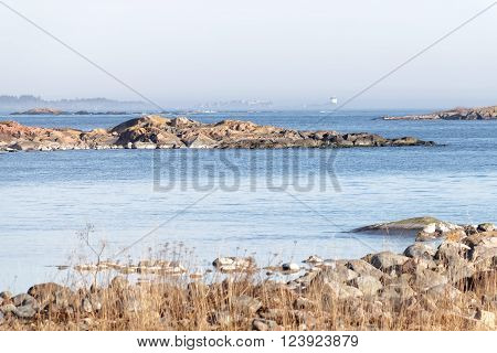 Coast, cliffs, islands and a distant beacon surrounded with fog a sunny day during spring time in scandinav