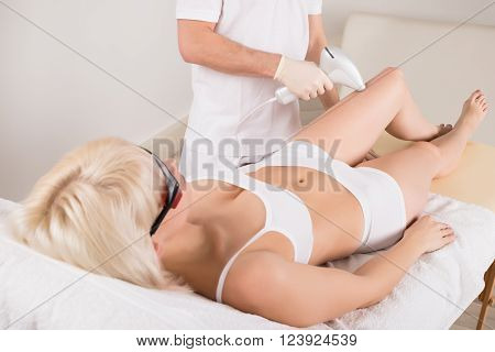 Woman Receiving Epilation Treatment On Legs At Spa