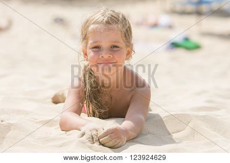 Pretty Girls Four Years Lying In The Sand On His Stomach On The Beach On A Sunny Day