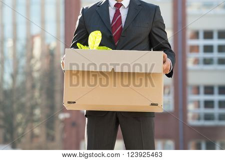 Close-up Of Businessperson Standing With Cardboard Box Outside O