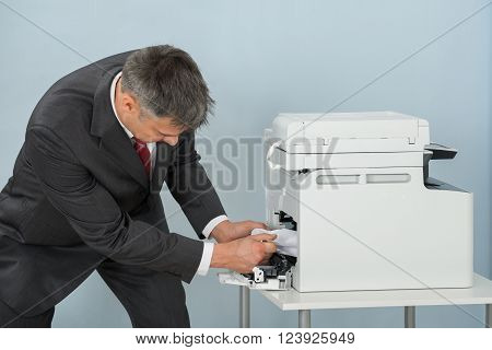 Businessman Removing Paper Stuck In Printer At Office