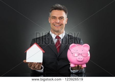 Mature Happy Businessman Holding Piggy Bank And House Model