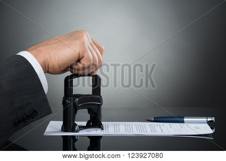 Businessman Stamping Contract Document At Office Desk