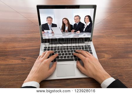 Close-up Of Businessman Video Conferencing On Laptop At Desk In Office