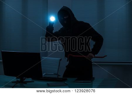 Thief With Flashlight And Crowbar Standing In Office