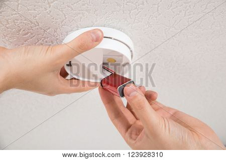 Close-up Photo Of Handyman Repairing Smoke Detector