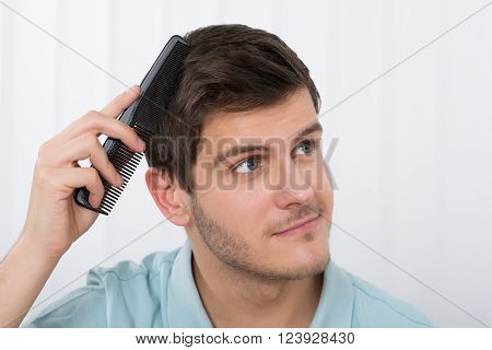 Close-up Of Young Man Combing His Hair With Comb