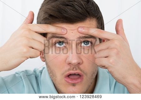 Shocked Young Man Looking At Pimple On Forehead