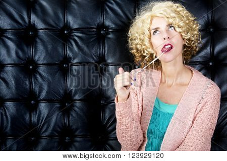 portarit of blond curly woman with bubblegum in front of black leather background