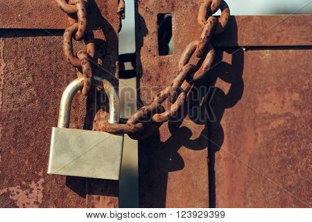 Padlock with shackle and locking mechanism closeup one portable lock on chain on unpainted rusty metal gate doors outdoor on blurred background
