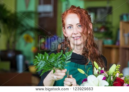Mature adult with fern greens preparing a floral arrangement in florist shop