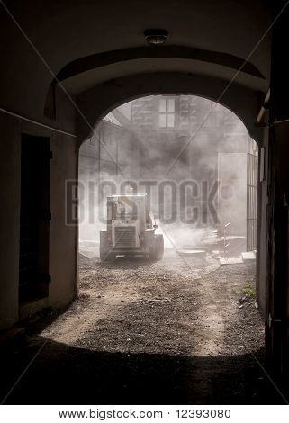 Heavy moving equipment in dust cloud captured in the frame of a gate.