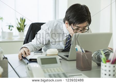 The businessman who is surprised to look at the note PC
