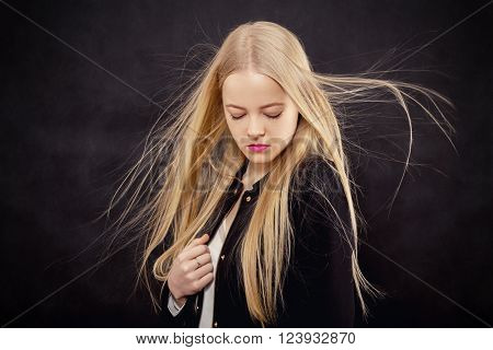 sad blond girl with flying hair on black background