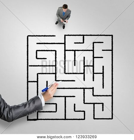 Top view of businessman with cup of coffee and drawn maze on floor